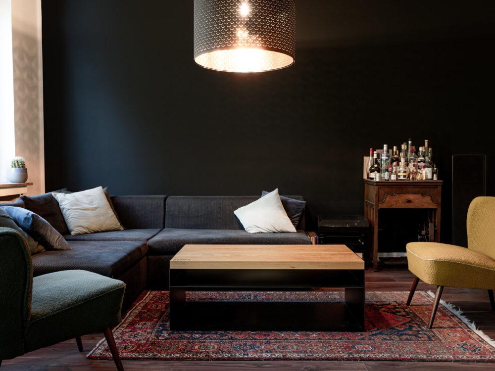 Das BIld zeigt den Couchtisch 'Anno 73' von OPA ERWIN in Szene. Der Tisch steht in einem Wohnzimmer vor einem Sofa mit zwei Sesseln. Im Hintergrund ist ein kleiner Schrank mit Spirituosen zu sehen. Oben im Bild ist eine Wohnzimmerlampe zu sehen, links im Bild ist ein Fenster angeschnitten.