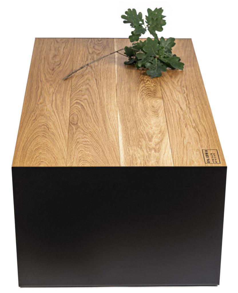 Das Bild zeigt den Couchtisch 'Anno 73' von OPA ERWIN. Das Massivholzmöbel wird von der kurzen Seite gezeigt mit weißem Hintergrund. Auf der Eichen Tischoberfläche liegt ein Eichenzweig mit grünen Blättern.